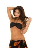 Женщина в черной верхней части бикини и саронг вокруг рук талии в волосах Стоковая Фотография