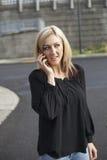 Женщина в черной верхней части говоря на сотовом телефоне стоковое изображение
