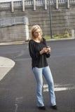 Женщина в черной верхней части отправляя СМС на сотовом телефоне стоковое фото rf