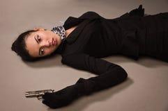 Женщина в черном костюме при оружие лежа на поле Стоковое фото RF