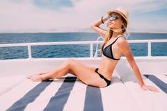 Женщина в черном купальнике лежа на палубе яхты на море солнечного летнего дня красивом на предпосылке Стоковые Фотографии RF