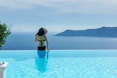 Женщина в черном купальном костюме и шляпе Стоковые Фото