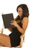 Женщина в черном обмундировании сидит чтение книги Стоковая Фотография