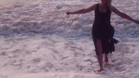 Женщина в черном платье бежит к ее стороне распространяя ее оружия для того чтобы обнять, на море, большие волны видеоматериал