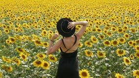 Женщина в черном платье и шляпе идет сток-видео