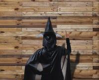 Женщина в черном страшном костюме хеллоуина ведьмы с деревянным PA стены Стоковые Фото