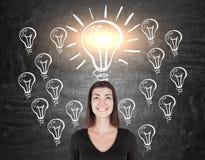 Женщина в черноте и много эскизов электрической лампочки Стоковое фото RF