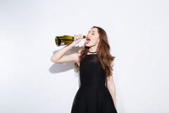 Женщина в шампанском черного платья выпивая от бутылки Стоковое Изображение