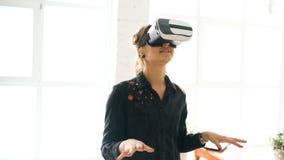 Женщина в шлемофоне VR смотря вверх и пробуя касаться объекты в виртуальной реальности дома внутри помещения стоковые изображения rf