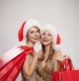 Женщина 2 в шляпах santa держа красные хозяйственные сумки стоковые фото