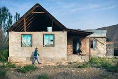 Женщина в шляпе идя около старого дома Стоковое Изображение