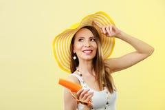 Женщина в шляпе лета держит лосьон солнцезащитного крема солнечных очков Стоковое Изображение