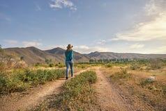 Женщина в шляпе на проселочной дороге Стоковые Изображения