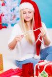 Женщина в шляпе Санты подготавливая подарки рождества Стоковая Фотография