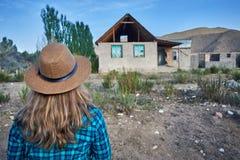Женщина в шляпе смотря старый дом стоковая фотография rf