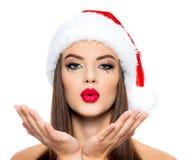 Женщина в шляпе santa отправляет поцелуй Сторона красивой женщины с ладонями около стороны с целуя знаком - изолированным на бело стоковая фотография