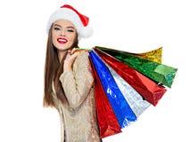 Женщина в шляпе santa с хозяйственными сумками стоковые изображения