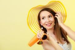Женщина в шляпе лета держит лосьон солнцезащитного крема солнечных очков Стоковая Фотография RF