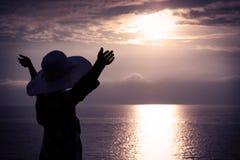 Женщина в шляпе при поднятые руки смотря заход солнца Стоковые Изображения RF