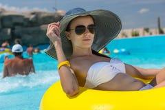 Женщина в шляпе Солнця плавая в автомобильную камеру бассейна Стоковое Фото