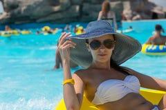 Женщина в шляпе Солнця плавая в автомобильную камеру бассейна Стоковые Фотографии RF
