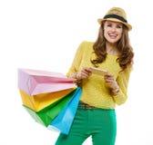 Женщина в шляпе с хозяйственными сумками писать sms на smartphone Стоковое Фото