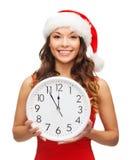 Женщина в шляпе хелпера santa при часы показывая 12 Стоковые Изображения RF