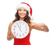 Женщина в шляпе хелпера santa при часы показывая 12 Стоковая Фотография RF