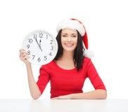 Женщина в шляпе хелпера santa при часы показывая 12 Стоковые Фотографии RF