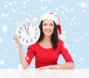 Женщина в шляпе хелпера santa при часы показывая 12 Стоковое Изображение