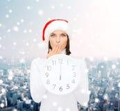 Женщина в шляпе хелпера santa при часы показывая 12 Стоковые Изображения