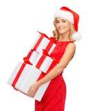 Женщина в шляпе хелпера santa с много подарочных коробок Стоковая Фотография