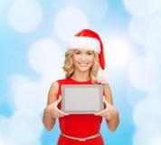 Женщина в шляпе хелпера santa с ПК таблетки Стоковая Фотография RF