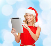 Женщина в шляпе хелпера santa с ПК таблетки Стоковое Изображение