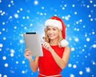 Женщина в шляпе хелпера santa с ПК таблетки Стоковые Фотографии RF