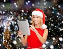 Женщина в шляпе хелпера santa с ПК таблетки Стоковые Изображения RF
