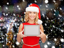 Женщина в шляпе хелпера santa с ПК таблетки Стоковое Фото