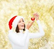 Женщина в шляпе хелпера santa с шариком рождества Стоковые Фотографии RF