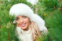 Женщина в шляпе, mittens, шарфы, свитеры, мех в лесе ели зимы стоковые изображения
