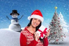Женщина в шляпе santa держа подарок рождества против цифров произведенной предпосылки Стоковая Фотография