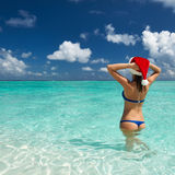 Женщина в шляпе santa на пляже Стоковые Изображения RF