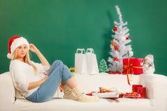 Женщина в шляпе santa ослабляя на софе Стоковое фото RF
