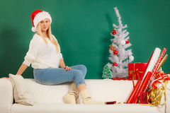 Женщина в шляпе santa ослабляя на софе Стоковая Фотография