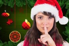 Женщина в шляпе santa с пальцем на губе против цифров произведенной предпосылки рождества Стоковая Фотография