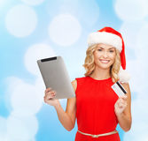 Женщина в шляпе santa с ПК и кредитной карточкой таблетки Стоковое фото RF
