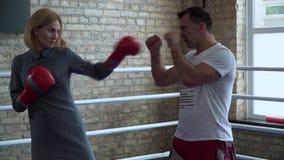 Женщина в элегантном платье, перчатках бокса тренируя на боксерском ринге с тренером сток-видео