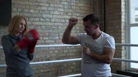 Женщина в элегантном платье, перчатках бокса тренируя с тренером на боксерском ринге сток-видео