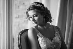 Женщина в bridal платье сидя на кресле Смотреть вниз Крытый, внутренний, студия стоковая фотография rf