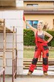 Женщина в dungarees работая на строительной площадке стоковые фотографии rf