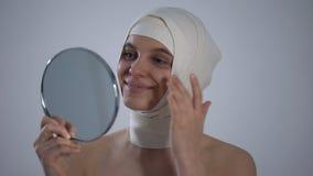 Женщина в headwrap смотря отражение зеркала, удовлетворяемое с пластической хирургией видеоматериал